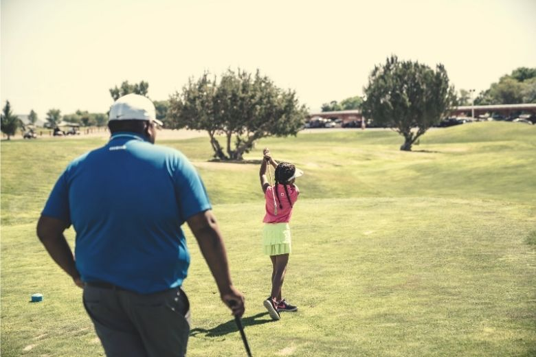 A young girl playing golf